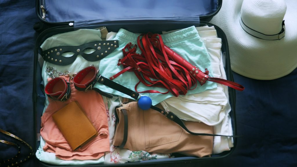 Kinky sex toys on top of clothes in an open suitcase