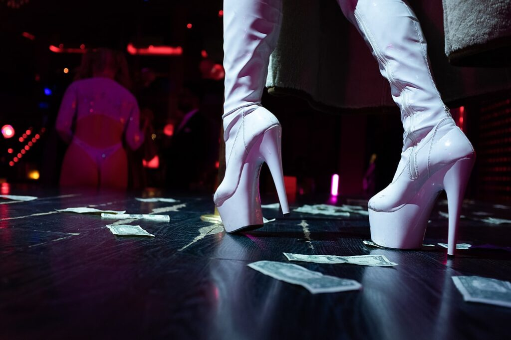 A close-up of white high-heeled boots on a stage surrounded by dollar bills.
